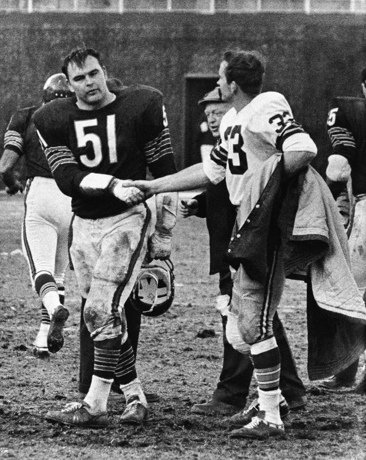 A little rivalry never got in the way of friendship. Dick Butkus shakes hands with former college teammate Jim Grabowski after a tough Pakcers-Bears matchup.
