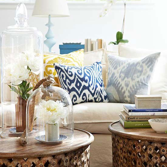 Patterned pillows in sunny yellow, royal blue and soft blue-gray add warmth to the home's all-white color scheme. A mix of rustic textures, such as unfinished woods, wicker, and wrought iron, add visual weight to the light, bright spaces. In the living room, a pair of timeworn wooden tables work together to function as a central coffee table.