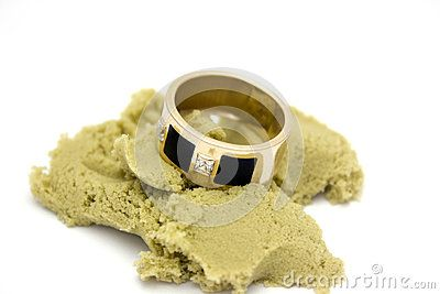 Ring with diamonds lays on peace of kinetic sand