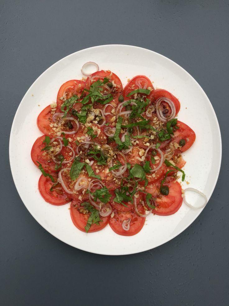 Tomaten salade Snijd de tomaten in plakjes, verdeel er een sjalot in ringetjes over. Doe er wat kappertjes op en bedruppel met een dressing van 3 el olijfolie en 2 tl balsamico, peper en zout. Strooi er basilicum in reepjes over en als laatste broodkruim (verkruimel 1 of 2 sneetjes wit brood in de keukenmachine, verhit 1 el olijfolie in een koekenpan en fruit hier een knoflookteen in. Haal de knoflook eruit en pak het broodkruim in de knoflookolie al omscheppend bruin)