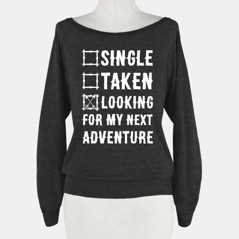 """This traveler's shirt is perfect for any wanderlust queen. Show that you heart belongs to no one but the open road. This fun road trip shirt features and illustration of crossed arrows and the phrase """"Single, Taken, Looking for my Next Adventure"""""""