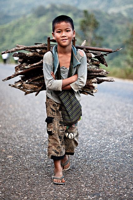 Boy with firewood, Laos. Children work all around the world; it is important to know the difference between children helping their family and children working at jobs.