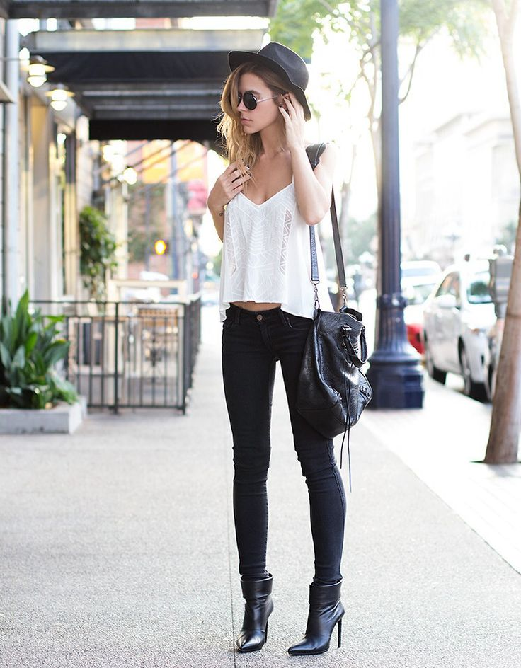 Jasmin Howell keeps it simple, wearing black jeans with a white long sleeved top, patent leather heels, and a petite cross body bag. Jasmin adds a touch of glamour to this look with black shades. Jasmin adds a touch of glamour to this look with black shades.