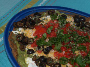 This is a wonderful bean dip to make for a tailgate party, refried beans, sour cream, cheese, green onions, and so much more make for a savory bean dip that everyone will enjoy.