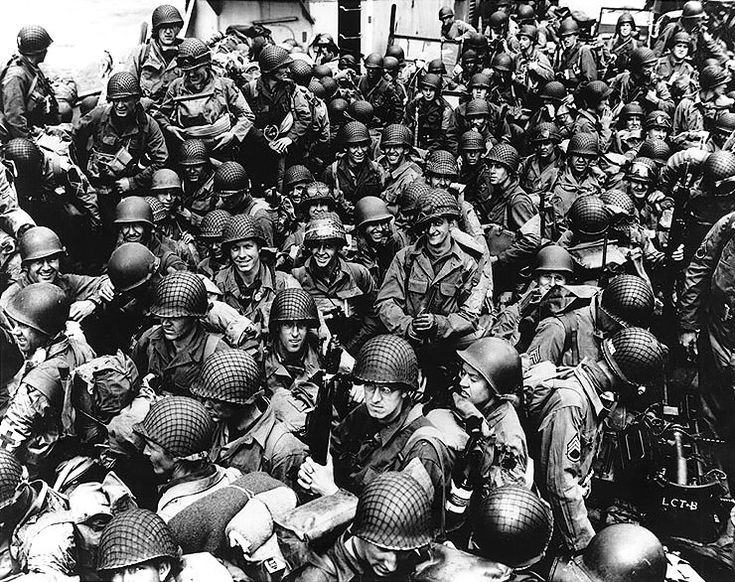 Army troops on board a LCT, ready to ride across the English Channel to France. Some of these men wear 101st Airborne Division insignia. 12 June 1944.