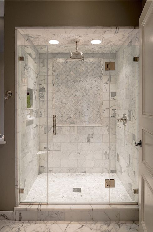 Incredible glass front shower with calacatta marble tiled interior accented with a panel of mosaic marble tile below a marble tiled ceiling finished with a rainfall shower head with recessed tiled niche to the left over marble mosaic tiled floors.