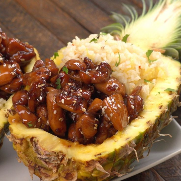 Pineapple cut into boat and stuffed with teriyaki chicken and pineapple rice