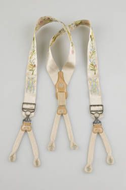 1880 Suspenders of white satin with floral embroidery done in green, blue, pink, and yellow. Monogram of wearer's initials 'GWM' on both sides at front, just above attached metal buckles. Braided straps