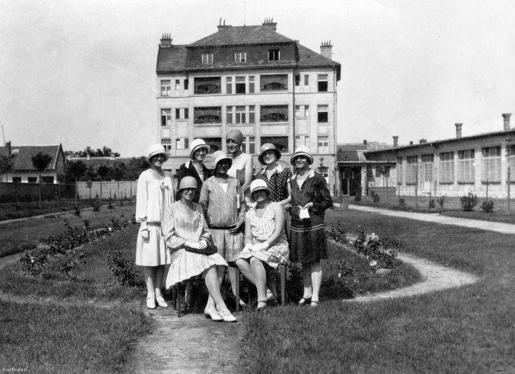 Kalap- és mosolytenger a Guttmann és Fekete harisnya-, kötszövött és kötöttárugyár munkáslakóháza előtt, 1932Az óbudai Vihar és Veder utca kereszteződésénél 1927-ben épült modern telepen az üzemcsarnok mellett állt a technikai személyzet többemeletes lakóháza. A parkosított, rózsatövekkel beültetett kertben nyolc, a némafilmkorszak eleganciáját felvonultató hölgy pillant a kamerába. A kalaporgia megpróbálja elterelni a figyelmünket a munkáslányok selyemharisnyájának diszkrét csillogásáról,
