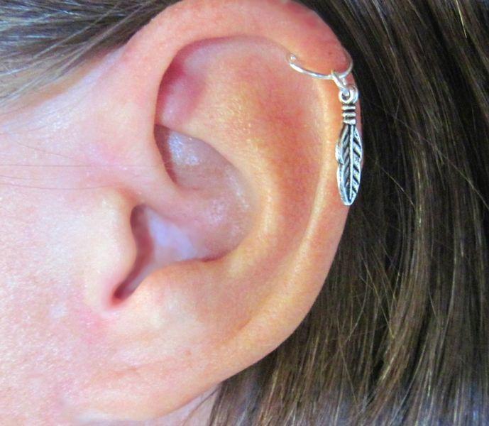 Chica con un piercing en la oreja en forma de pluma
