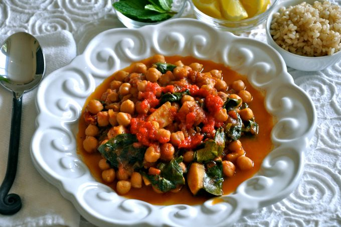 There is something about the combination of these Mediterranean ingredients and the accouterments that turns this simple chickpea dish into an exquisite dinner. I like to serve it with with lemon wedges, fresh mint and a dollop of roasted red pepper puree with a side of brown rice.