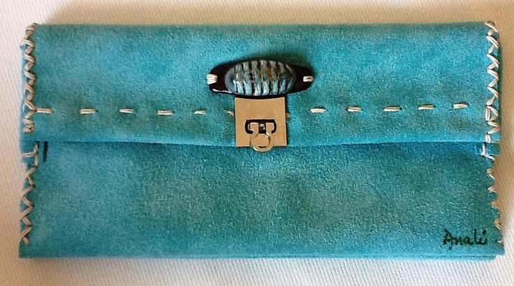 Small leather purse made in aqua blue color with internal division and adorned with small sea cockroach over coconut stick. Magnetic closure.