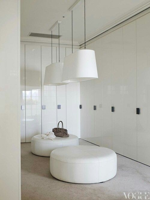 white walk in robe with ottomans + pendant lighting. Heaven.
