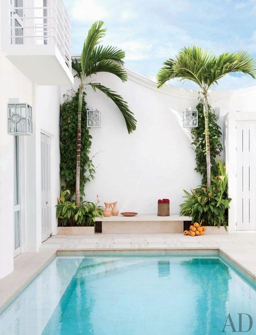 La piscina en la escapada Colombiana de Nueva York el diseñador de interiores Richard Mishaan está a la sombra de palmeras. Situada en la zona norte del país Cartagena,.The pool at the Colombian getaway of New York interior designer Richard Mishaan is shaded with palms