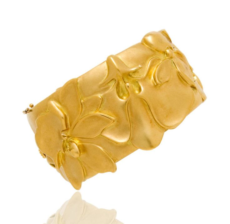An eighteen karat gold bangle bracelet, Angela Cummings for Tiffany & Co., 1983  the hinged form depicting a variety of high relief blossoms; signed Tiffany & Co. and Cummings, dated 1983; gross weight approximately: 115.4 grams; diameter: 2 1/4in.
