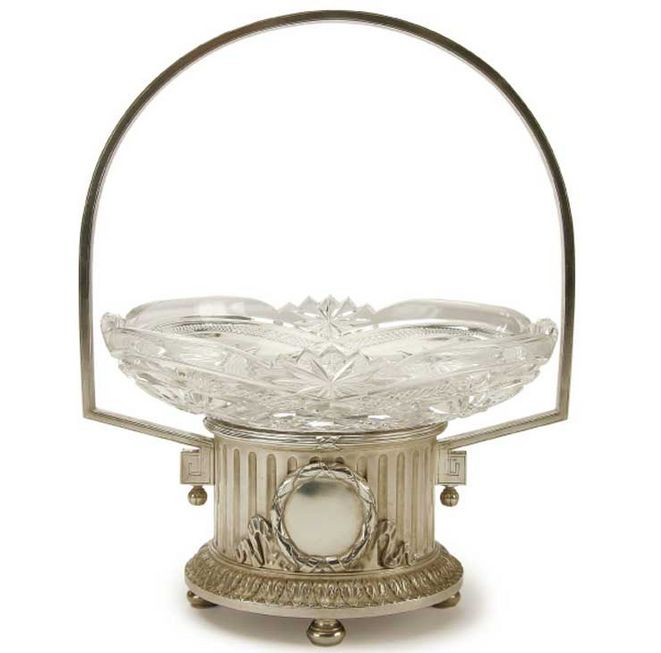 A LARGE FABERGE SILVER AND CUT GLASS CENTERPIECE BASKETRY BOWL. Moscow circa 1899-1908.  The fluted cylindrical base resting on four bun feet with acanthus skirt and with blank circular cartouche on both sides within laurels and ribbons.  The rim with banded reeds and the side set with arms supporting a large arched handle with glass insert deeply cut with geometric designs.
