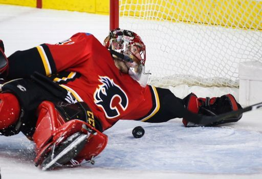 Calgary Flames goalie Mike Smith falls back on the puck as it slips past him during the first period of an NHL hockey game against the Detroit Red Wings on Thursday, Nov. 9, 2017, in Calgary, Alberta. (Jeff McIntosh/The Canadian Press via AP)