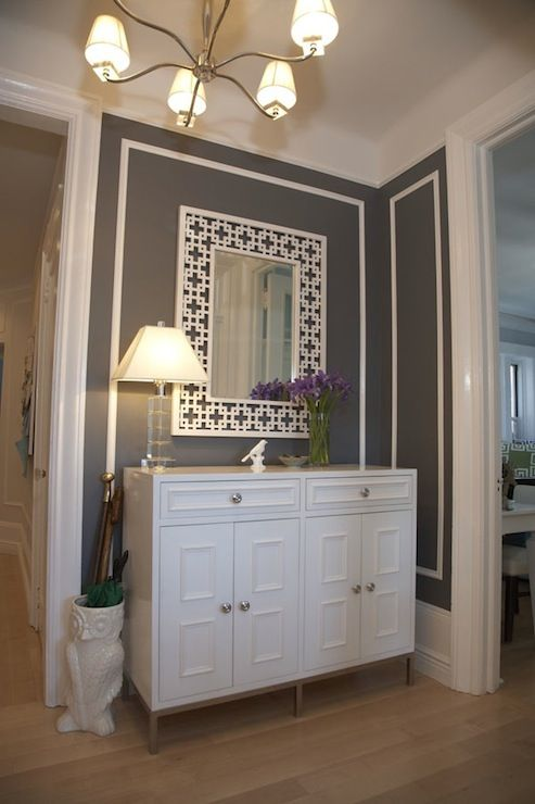 Gorgeous entryway with a stunning contemporary chandelier highlighting crisp white wood mouldings upon elegant grey walls