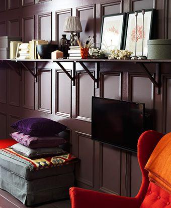 Malet væg med IKEA hylde. Nedenunder er der en lænestol og en puf med puder.