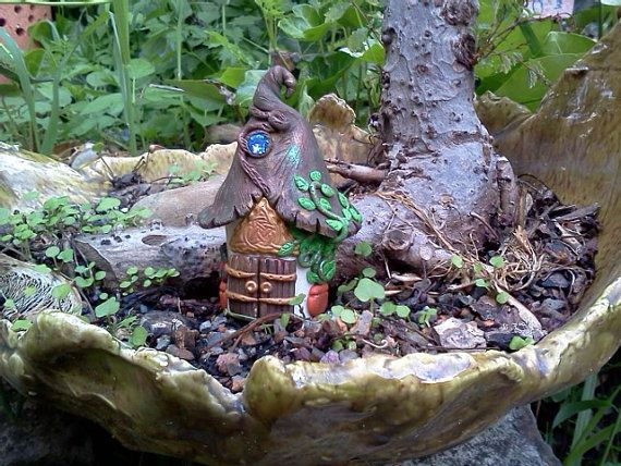 This cute little Celtic Fairy Garden House was hand sculpted from polymer clay. A Celtic Triskel sits above the double wood style doors, and welcomes all whom enter. Three little terracotta pots filled with greenery decorate the outside of the home, and keep your fairies favorite herbs close by. The rustic roof has a lovely sparkling blue crystal set into it. A bit of PearlEx powder was added to the clay in order to give the house an ethereal quality.  This house is approximately 3 tall, and…