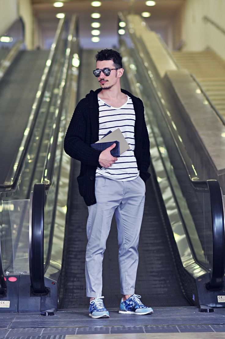 Shop this look for $205: http://lookastic.com/men/looks/shawl-cardigan-and-v-neck-t-shirt-and-zip-pouch-and-chinos-and-athletic-shoes/2852 — Black Shawl Cardigan — White and Black Horizontal Striped V-neck T-shirt — Navy Leather Zip Pouch — Grey Chinos — Blue Camouflage Athletic Shoes