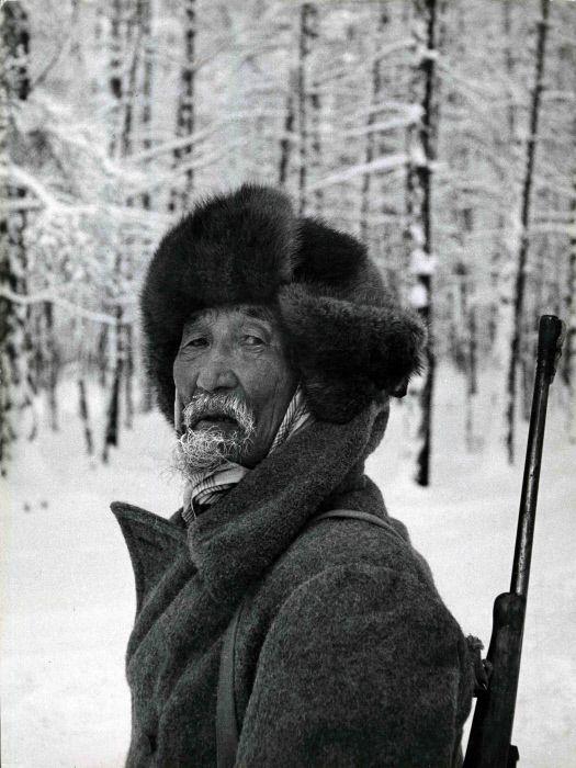 rimo piano di un anziano cacciatore siberiano, mentre guarda il fotografo. Alle sue spalle una foresta innevata. Siberia, 1972.  ©Mondadori Portfolio/Mario de Biasi
