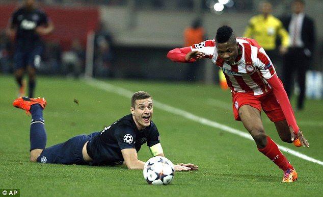 Olympiacos' Michael Olaitan skips past Nemanja Vidic as the Serbian looks on