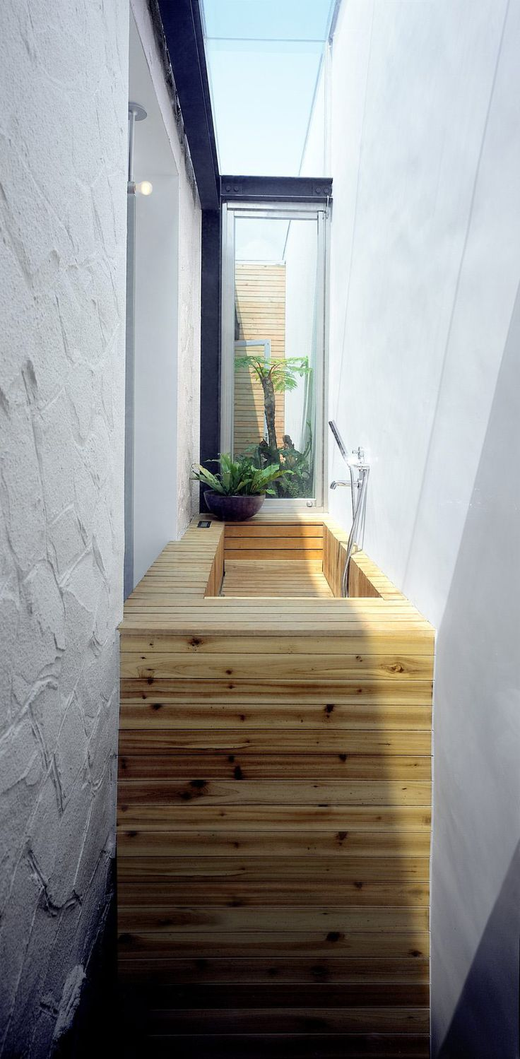wooden tub tucked into a narrow space. Notice the different textures of materials too. Elegant design.