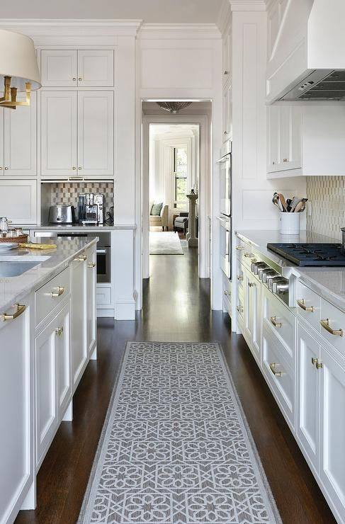 Stunning white kitchen boasts a gray trellis runner placed between white shaker cabinets adorning brass pulls and white marble countertops.