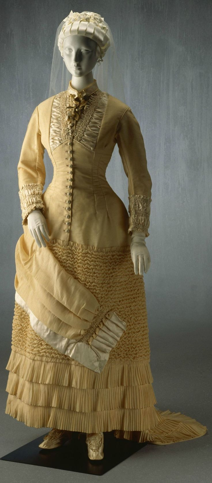 "Wedding Dress: 1882, wool, silk, cotton. ""This dress was worn by Hannah Palser Prior for her marriage to Alfred Matthew Adlam at the Holy Trinity Church, Kelso, near Bathurst on 16 August 1882. The dress is remarkably elaborate for a simple country wedding. Its complicated cut and construction, with slim-fitting bodice and detailed trimmings, suggests the work of a professional dressmaker."""