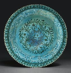 A KASHAN TURQUOISE AND BLACK PIERCED POTTERY BOWL CENTRAL IRAN, LATE 12TH OR 13TH CENTURY