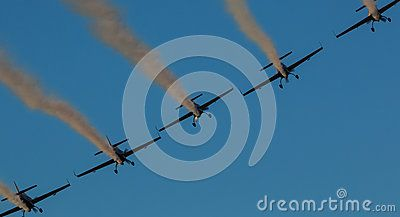 A team of five airplanes in yellow flying together high up in the sky on an air show.  Airplanes on air show with smoke trails. Airplane performing difficult maneuver in the sky. Blue clear sky. Blue background.