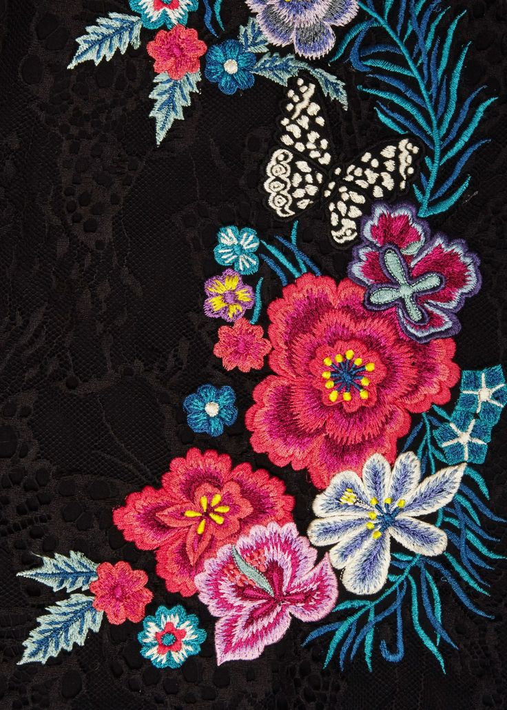Close up detail of the Matthew Williamson Floral Embroidered Black Lace Dress. The little black dress is a perennial classic. Seen here in bespoke lace with floral and butterfly embroidery, it has a modern, sexy edge. We love how the embroidery is placed to enhance the contours of the body.