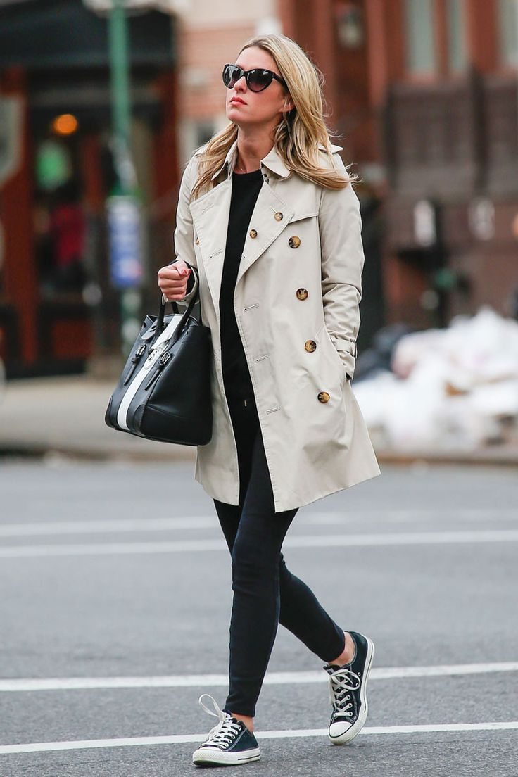 Nicky Hilton in all black, a trench coat, and Converse.
