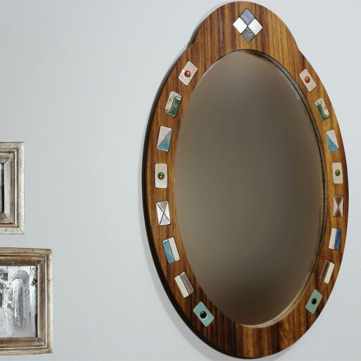 Handmade mirror made from iroko tree and surrounded by tiny ceramic tile. Section at the top of product resembles the king crown.