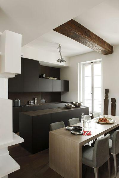 Une cuisine noire ouverte sur la salle à manger