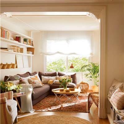 Salón con librería, sofá oscuro en L, mesa de centro redonda y alfombra rojiza (404512)