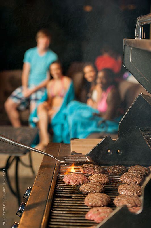 Hamburgers on the grill, with teens defocused in the background, during a summer pool party.