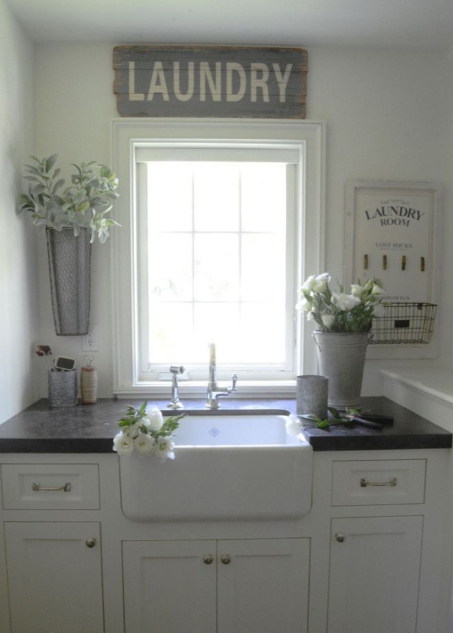 Laundry room with black leather finish granite, white farmhouse sink, white cabinets. Flooring: gray hexagon tile