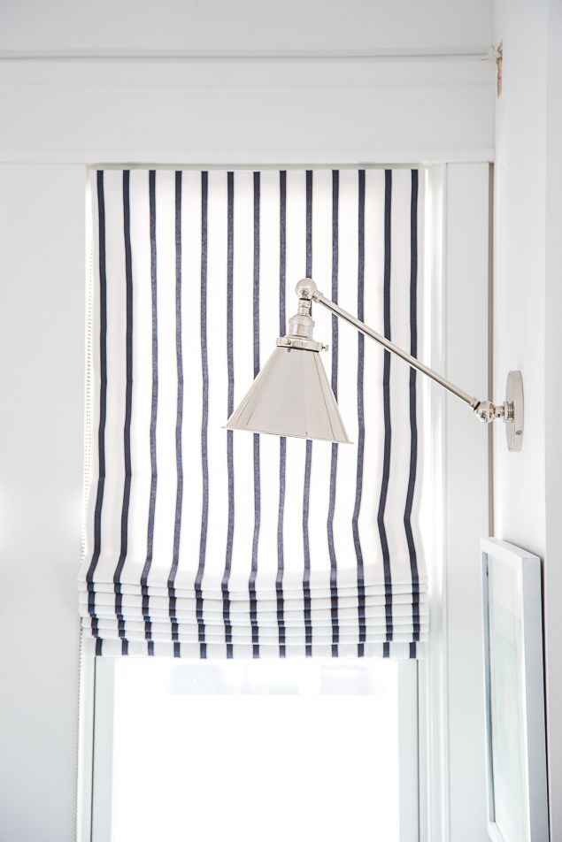 www.pencilshavingsstudio.com  Bright white living room with custom Sunbrella Lido stripe roman shades by Loom Decor. Swing arm library sconce in nickel by Restoration Hardware.. See the whole room at pencilshavingsstudio.com