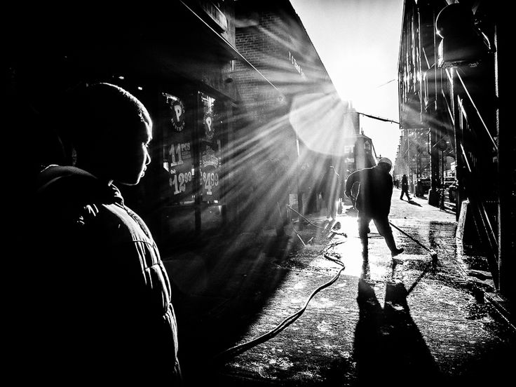 Nyc photography by jonathan auch giving a symbolic shot of the narrow alleys the light at the end but darkness covering everything except the straight