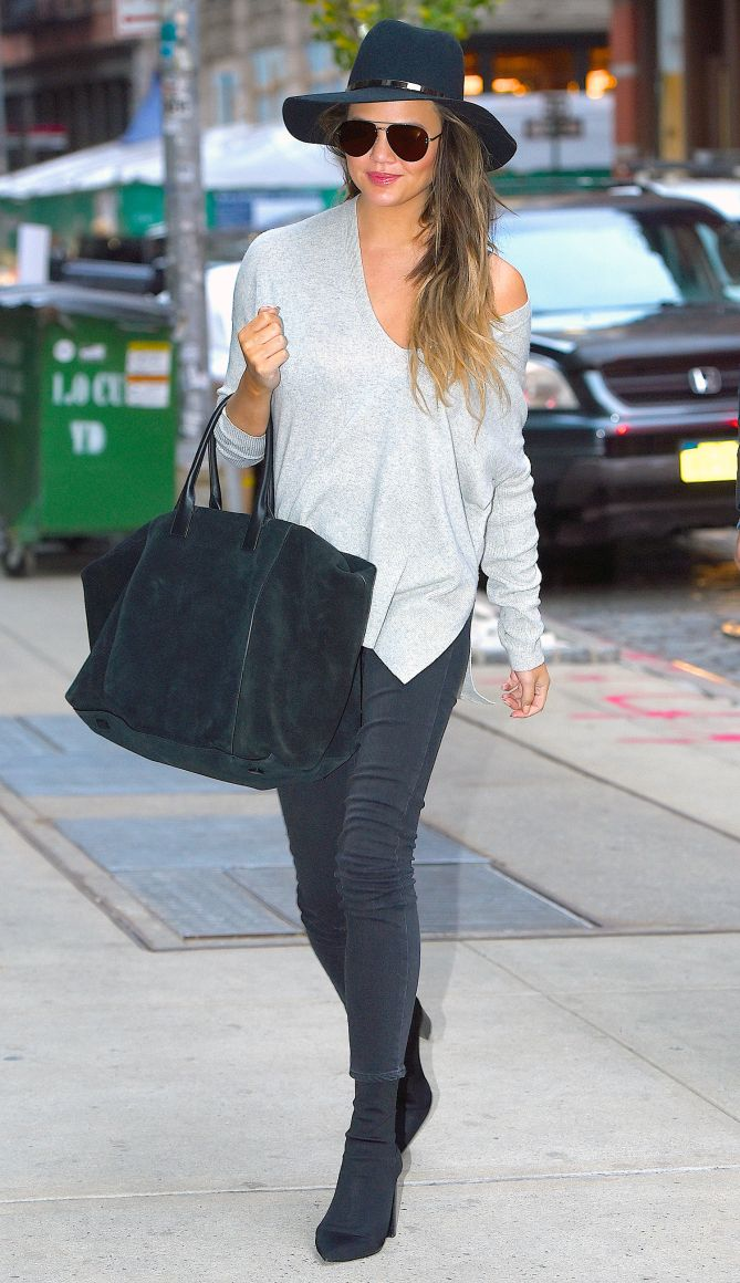 Chrissy Teigen in a gray off-the-shoulder sweater, gray jeans, booties and hat