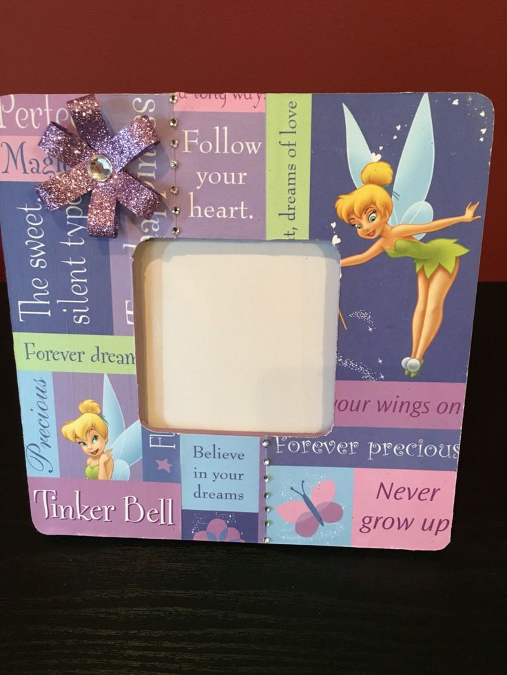 Adorable Disney Tinker Bell pink and purple frame.  This is a wood picture frame painted lavender, decorated by Tinker Bell paper decoupage with lots of cute sayings and inspuration. Then decorated with a sparkly lavender ribbon and lots of rhinestones for some sparkle!  Frame measures 7-3/4x7-3/4 with a picture opening of 3.7x3.7. Has square peg in the back to stand up frame.  Remember your Disney memories or celebrate your little Princess with this adorable frame