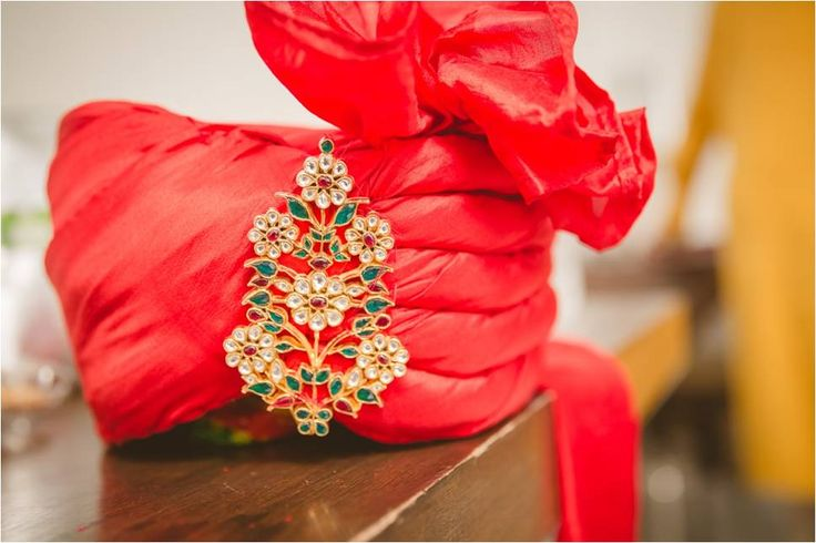 A traditional red saafa with floral brooch.
