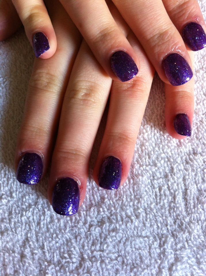 A set of acrylics with purple/blue sparkly nail polish