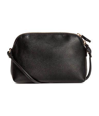 Siyah. İnce omuz askılı, üstte fermuarlı, bir adet fermuarlı iç bölmeli, küçük suni deri omuz çantası. Astarlı. Boyut 6x14x21 cm.