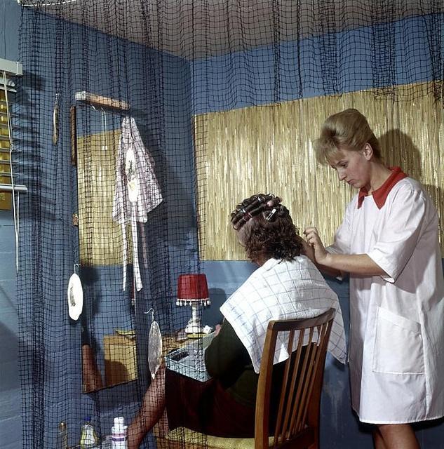 Woonarken, woonschepen. De kapster zet krulspelden in bij een andere vrouw, de kapperszaak bevindt zich op een woonboot, Nederland 1962.  English: Barber shop on a houseboat. The Netherlands, location unknown, 1962.