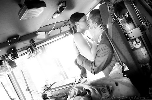 Firefighter and his bride share a kiss on their wedding day in a firetruck.