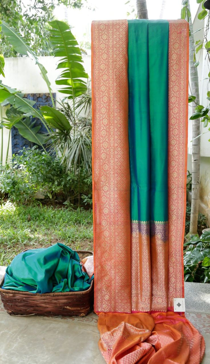 This Benares silk sari is in ocean blue. The border and pallu are in punch pink intricately woven with gold zari giving this simple sari a stylish touch.