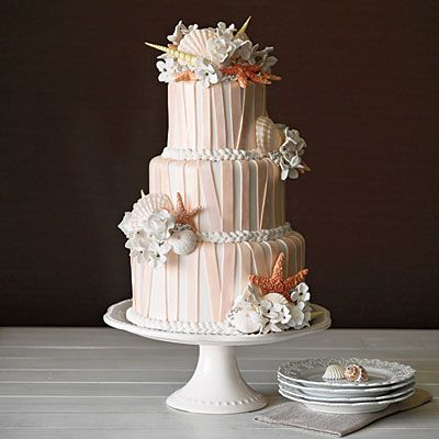 Seashells, starfish, flowers, and soft pink stripes adorn this beautiful beach wedding cake.